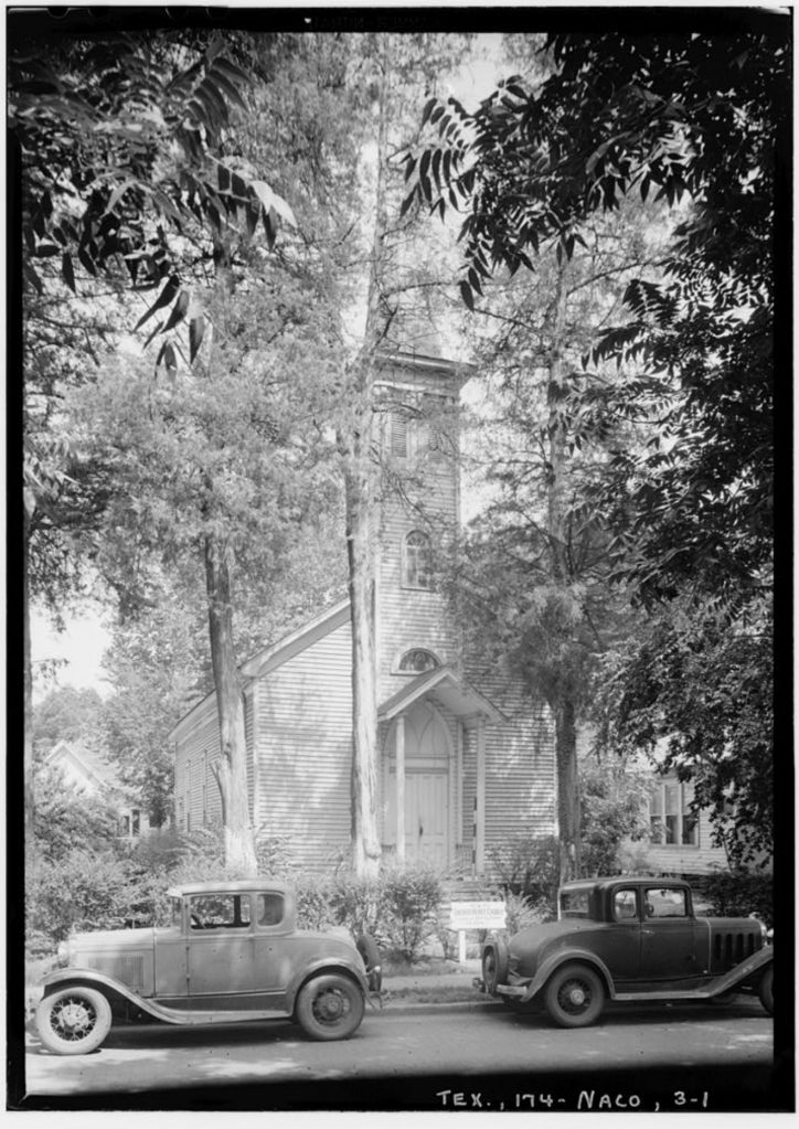 Image of historic church and old cars in the pine trees of Nacogdoches Texas.